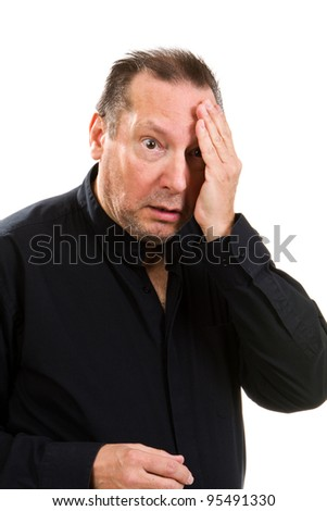 Man suffering from a headache holds his hand to his head in pain. - stock photo