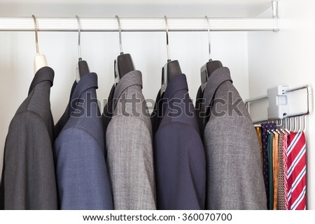 Man suits and ties inside a wardrobe - stock photo