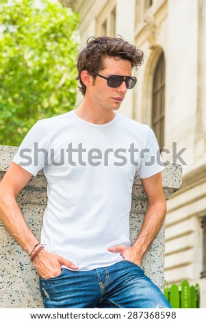 Man Summer Casual Street Fashion. Wearing White T shit, jeans, sunglasses, hands in pockets, a young European college student standing at corner on campus in New York, looking down, sad, thinking. - stock photo