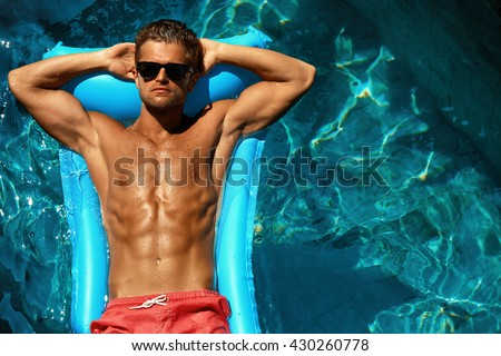 Man Summer Fashion. Beautiful Male With Sexy Body In Swimwear, Fashionable Sunglasses Tanning, Floating In Swimming Pool Water At Relax Spa Resort. Fitness Model With Skin Sun Tan Relaxing On Vacation - stock photo