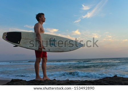 Man surfer with surfboard on a coastline. Bali. Indonesia - stock photo