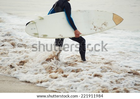 Man surfer with surfboard, surfer man carrying his surfing board, surfer in wetsuit holding a surfboard, surfer walking on the beach touching waves, surfer going to the water - stock photo