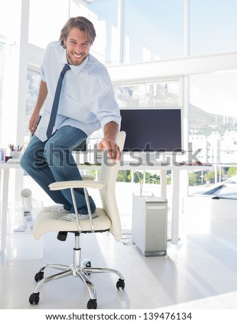 Man surfing his office chair and smiling in modern office - stock photo