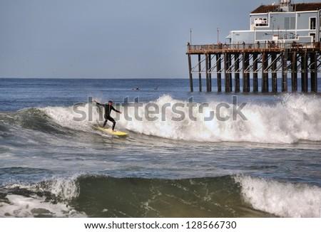 Man surfs a wave near a pier in Oceanside, California. - stock photo