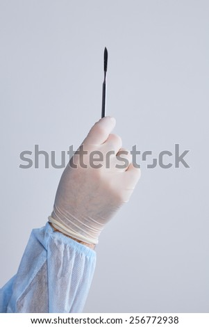 Man surgeon holds a scalpel in an operating room - stock photo