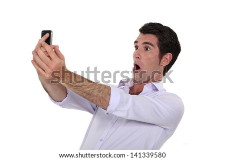 Man surprised watching his mobile phone - stock photo