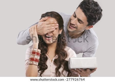 Man surprising a woman with a gift - stock photo