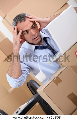 Man surrounded by boxes - stock photo