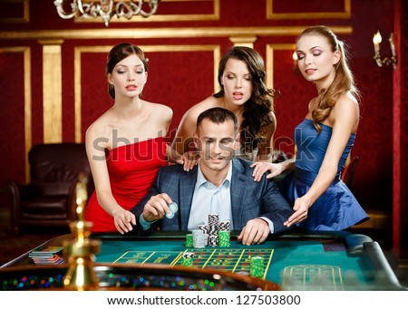 Man surrounded by girls plays roulette at the casino - stock photo