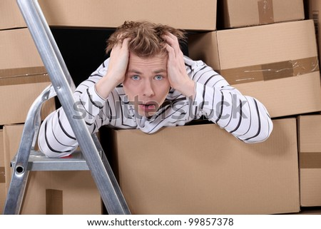 Man surrounded by stacks of cardboards - stock photo