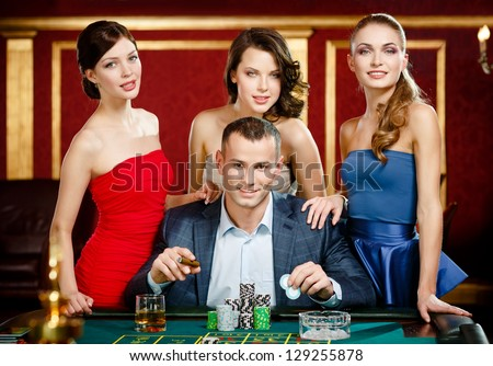 Man surrounded by women gambles roulette at the casino club - stock photo