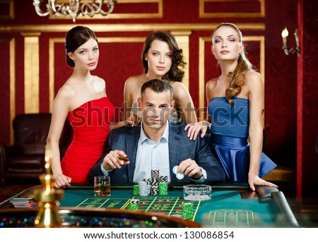 Man surrounded by women gambles roulette at the gambling house - stock photo