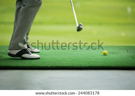 Man sweeping ball on golf course. Legs only - stock photo