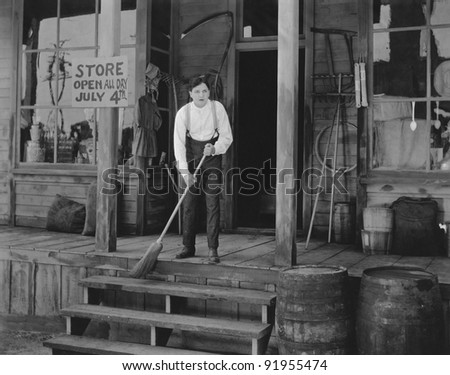 Man sweeping steps in front of store - stock photo