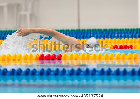 Man swimmer swimming crawl in blue water.