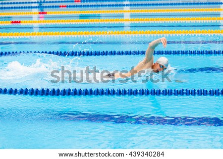 Man swimmer swimming crawl in blue water. - stock photo