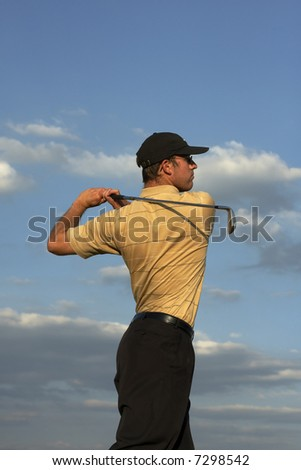 Man swinging a golf club late after noon