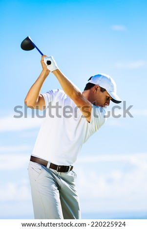 Man Swinging Golf Club with Blue Sky Background - stock photo