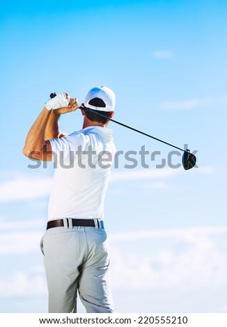 Man Swinging Golf Club with Blue Sky Background - stock photo