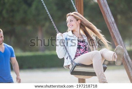 Man swinging his girl in a park - stock photo
