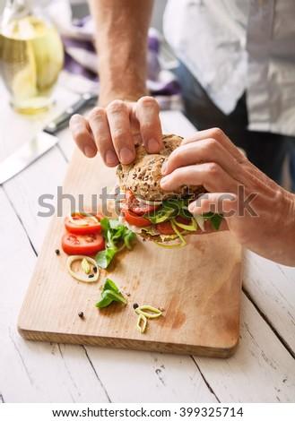 Man take a big sandwich in hands - stock photo