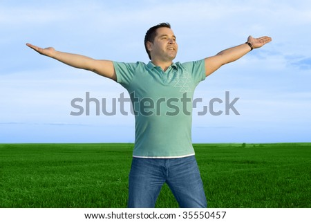 man take energy from nature in the meadow with dark blue sky - stock photo