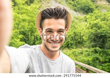 man takes a selfie in the nature - people, lifestyle and technology concept - stock photo