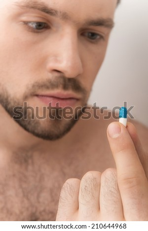 Man takes close up look at medicine. Sick man taking medicine in bedroom at home - stock photo