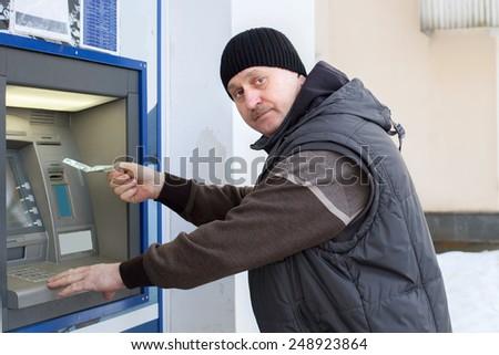 Man takes money at ATM - stock photo