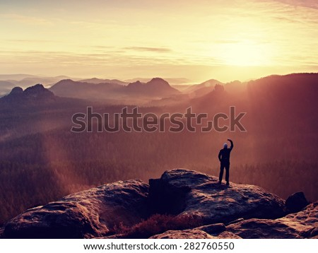 Man takes photos with smart phone on peak of rock empire. Dreamy fogy landscape, spring orange pink misty sunrise in a beautiful valley of rocky mountains. - stock photo
