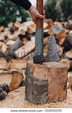 Man takes the ax from stump
