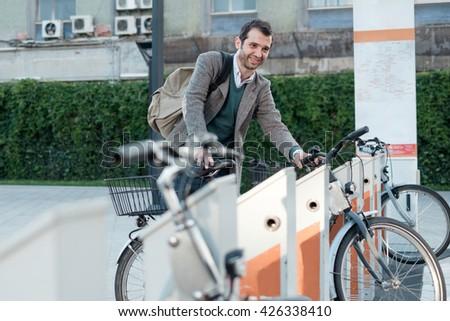man taking a bike in a bike sharing city service - stock photo