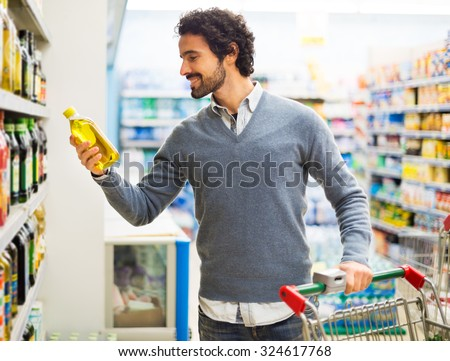 Man taking a bottle of oil from a shelf in a supermarket - stock photo