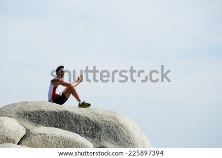 Man taking a break and relax sitting on mountain rock in the wonderful warm light of the sunny day, young man on sky nature background, healthy lifestyle concept, man enjoying to music in headphones - stock photo