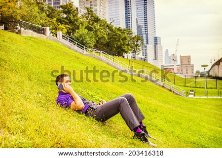 Man Taking a Break.  Dressing in a purple shirt, gray pants, a black tie, leather shoes, a young handsome businessman is lying on grasses, talking on a mobile phone. - stock photo