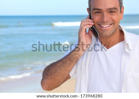 Man taking a call whilst at the beach - stock photo