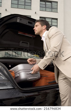 Man taking a luggage from a car trunk - stock photo