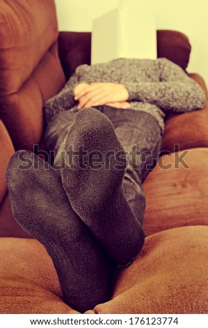 man taking a nap in a couch with a book covering his face - stock photo