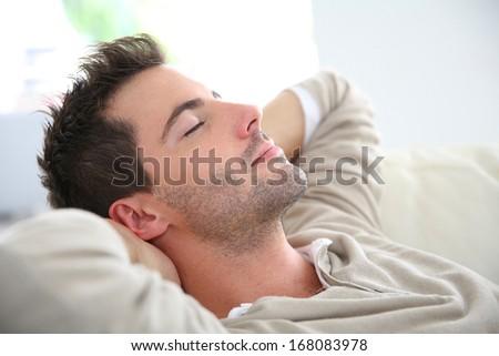 Man taking a nap in sofa - stock photo