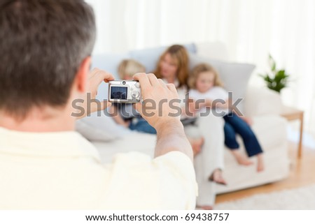 Man taking a photo of his family at home - stock photo