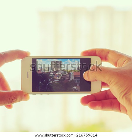 Man taking a photo with phone - instagram filter - stock photo