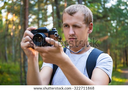 man taking a photo with retro camera in forest