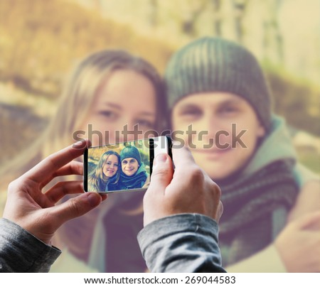 Man taking a picture of Happy couple. Instagram style filtred image