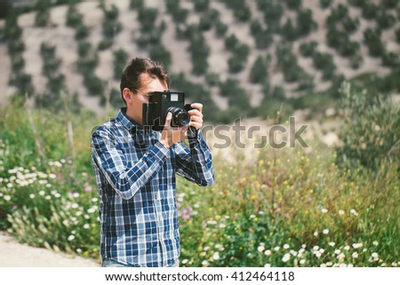 Man taking a picture with an old vintage camera in the countryside. - stock photo