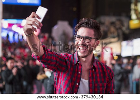 Man taking a selfie on Times Square, New York, at night in autumn - stock photo