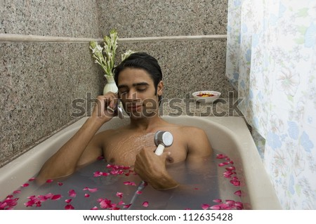 Man taking a shower and talking on a mobile phone - stock photo