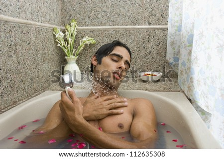 Man taking a shower in a bathtub - stock photo