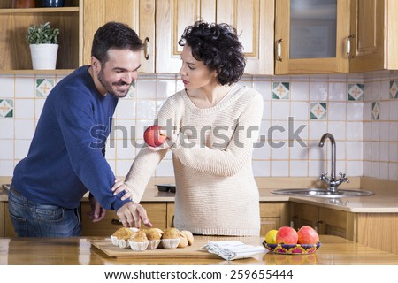 Man taking delicious cupcake while her woman offering him an apple. Concept of healthy food. Concept of temptation and meal - stock photo