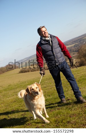 Man Taking Dog On Walk In Autumn Countryside - stock photo