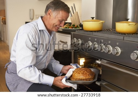 Man Taking Food Out Of The Oven